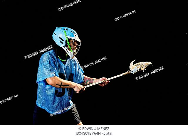 Young male lacrosse player poised with lacrosse stick, against black background