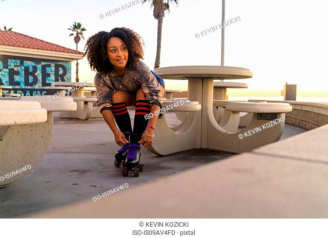 Mid adult woman sitting outdoors, tying rollerskates