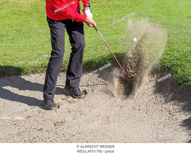 Golfer playing bunker shots, partial view