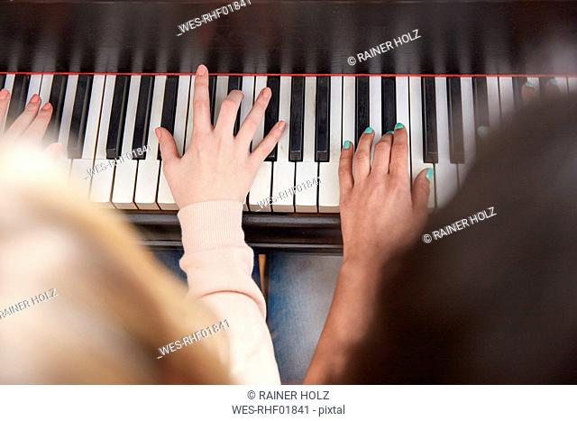 Close-up of two girls playing piano together