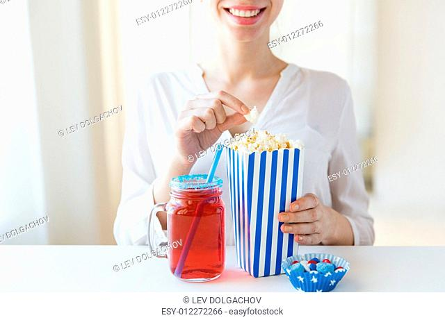 american independence day, celebration, patriotism and holidays concept - close up of woman eating popcorn with drink in glass mason jar and candies at 4th july...