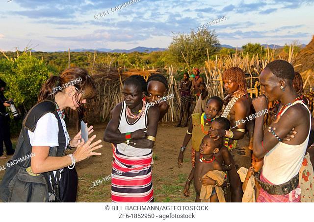 Turmi Ethiopia Africa Lower Omo Valley village with tourist showiing Digital tablet movie to Bena Tribe locals in village 24