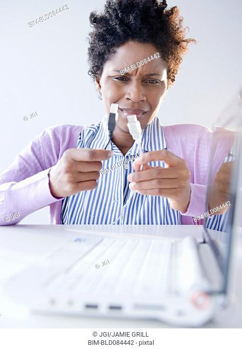 Confused Black woman looking at USB cables