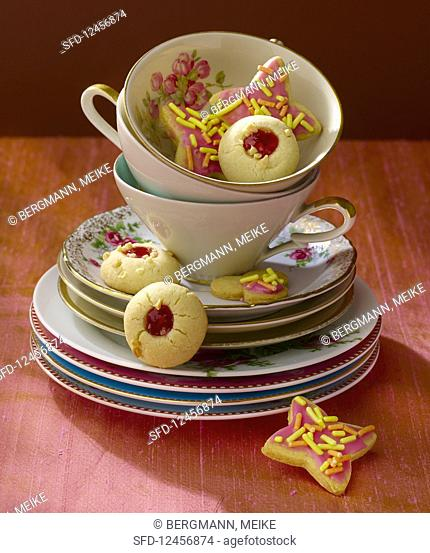 Shortbread jam biscuits and star-shaped biscuits in a stack of crockery