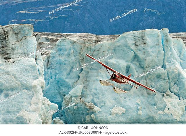 A DeHavilland Beaver flies over Strandline Lake at the edge of the Triumvirate Glacier in the Tordrillo Mountains, Southcentral Alaska, Fall
