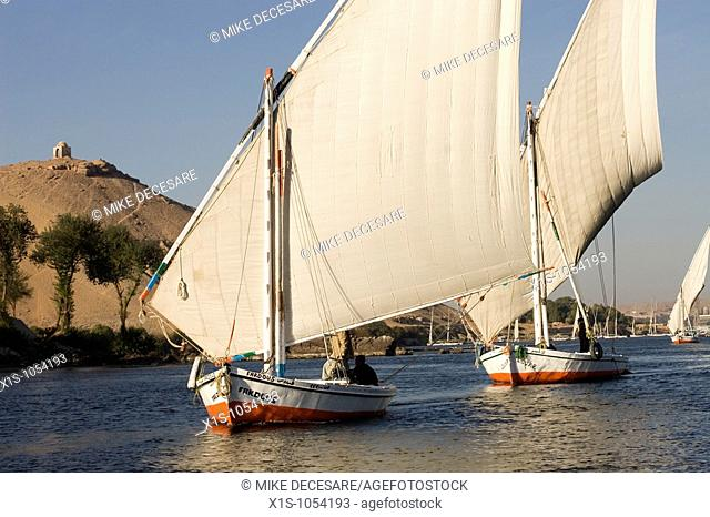 Low angle of several felucca boats in the Nile River with a temple on top of a hill in the background