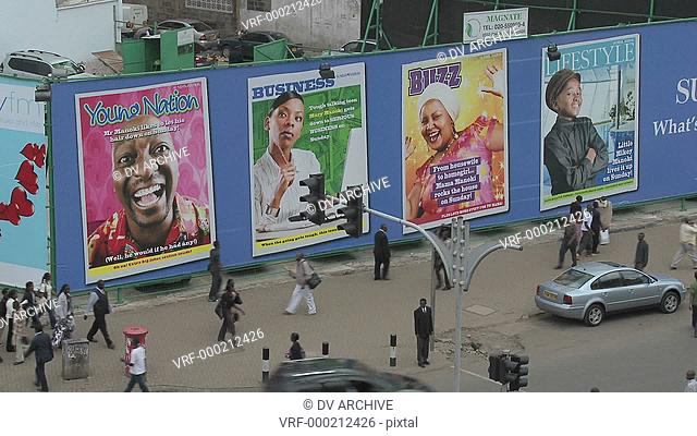 Handprinted billboard signs along a busy street in kenya