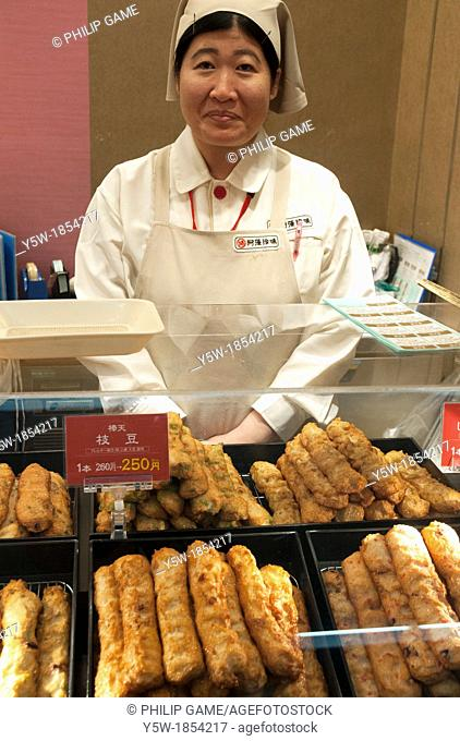 A woman sales assistant selling fried snack foods at a railway station in Japan