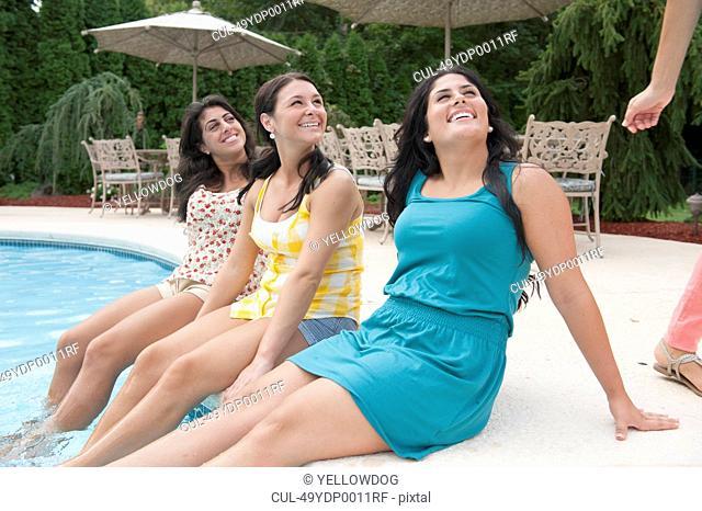 Women dangling feet in swimming pool