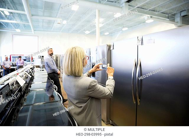 Senior woman with camera phone photographing refrigerator in appliance store