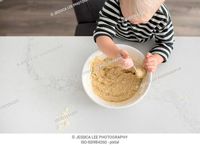 Young boy mixing mixture in mixing bowl, overhead view