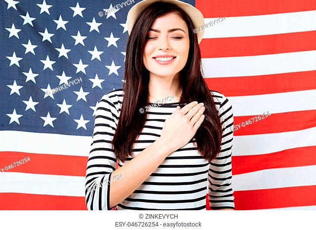 Promising love this country forever. Charismatic charming happy woman smiling and celebrating national holiday while standing with closed eyes against American...