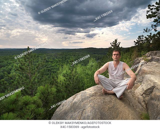 Young man meditating in the nature  Algonquin, Ontario, Canada