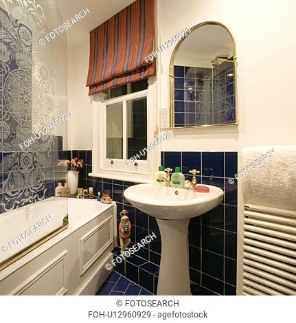 Red and blue striped blind on window of small bathroom with white pedestal basin and engraved glass panel on bath