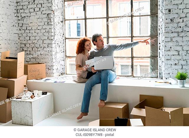 Couple moving into industrial style apartment, sitting on window ledge pointing