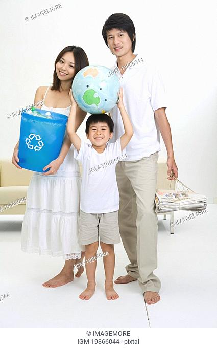 Young family with one child holding newspaper, globe and bottle bank