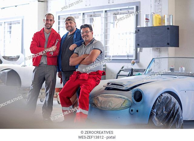 Car mechanics together in car restoration workshop