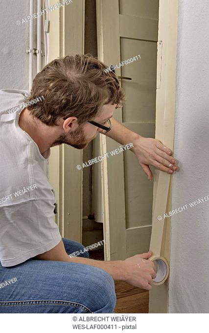 Young man masking door frame with adhesive tape