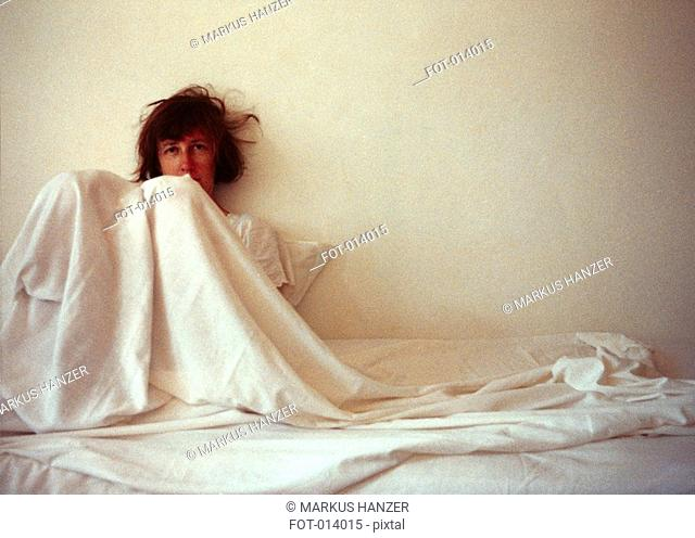 woman covered in sheets, leaning against the wall