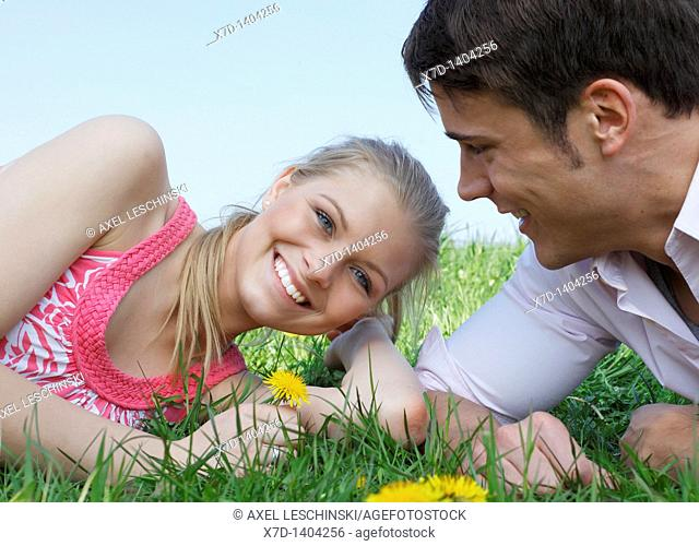 couple lying on a madow