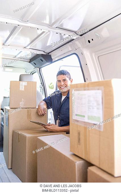 Hispanic deliveryman unloading van