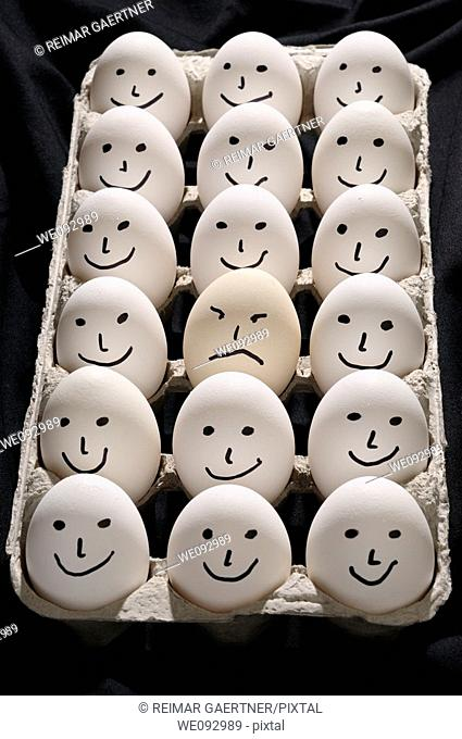 Package of backlit eggs on black cloth with smiling faces except for one grumpy sad face