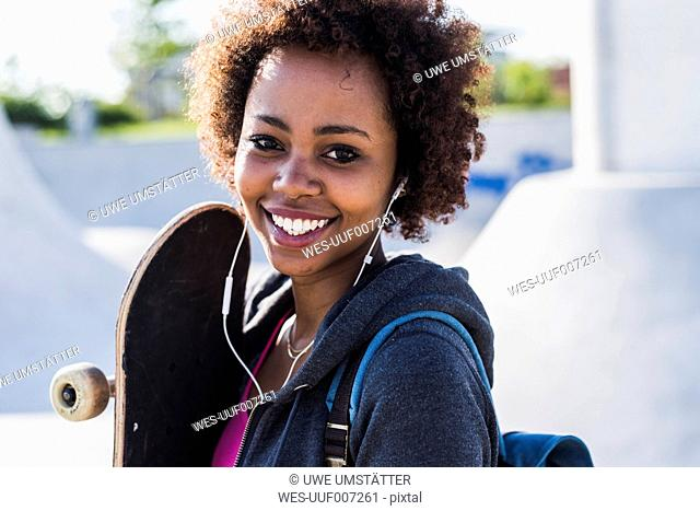 Portrait of smiling young woman with skateboard listening to music