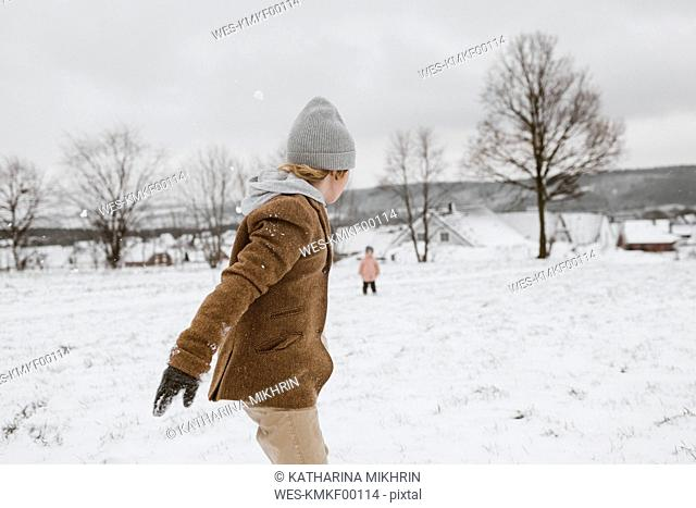 Boy and his little sister playing together in snow-covered landscape
