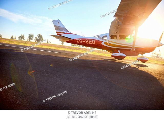 Propellor airplane landing on sunny tarmac