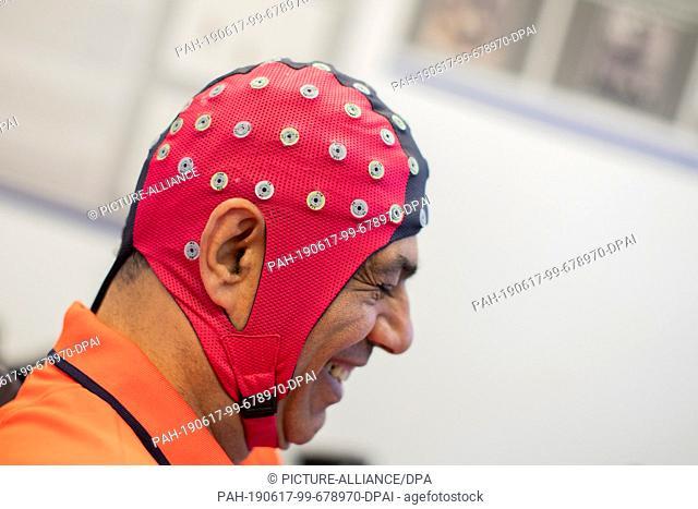 17 June 2019, North Rhine-Westphalia, Bochum: Sarshar Manoucheher, a paraplegic patient, smiles after using a brain-computer interface to steer his wheelchair...