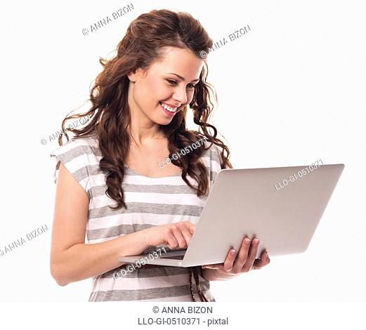 Happy young woman using laptop Debica, Poland