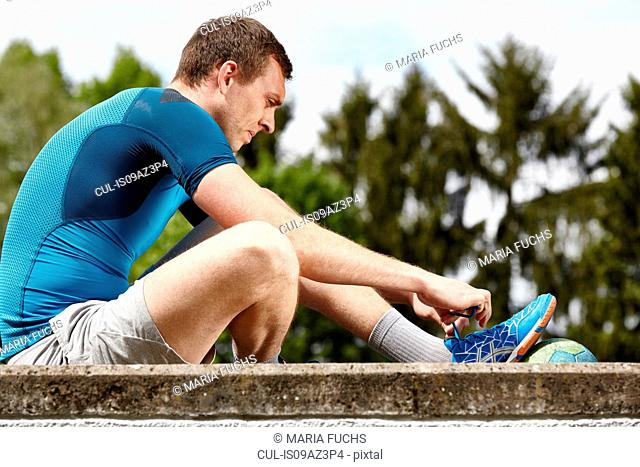 Young male handball player sitting on wall tying trainer laces