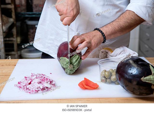 Cropped view of chef slicing aubergine
