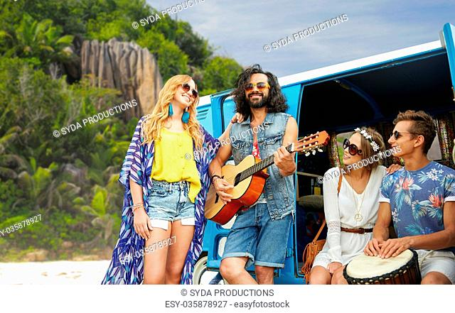summer holidays, road trip, travel and people concept - happy young hippie friends with guitar and drum playing music at minivan car over island beach...