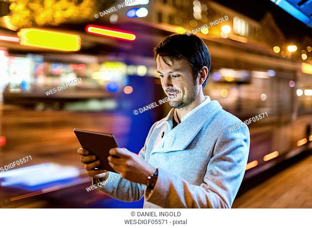 Portrait of smiling businessman looking at digital tablet on the street at night
