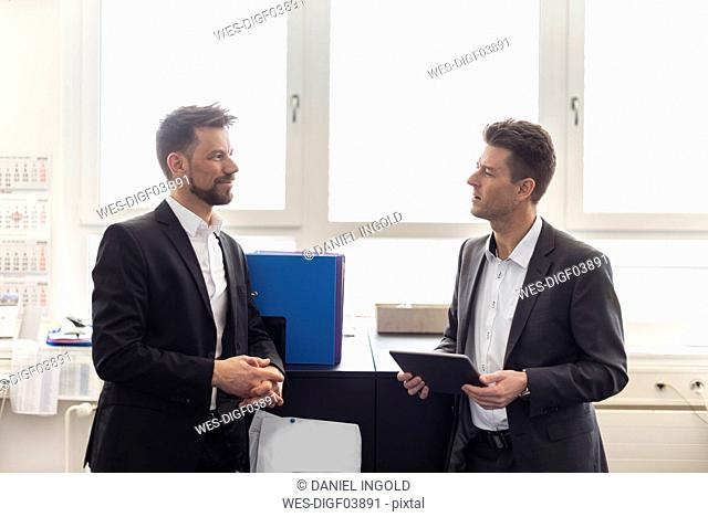 Two businessmen standing in office, discussing solutions, using digital tablet