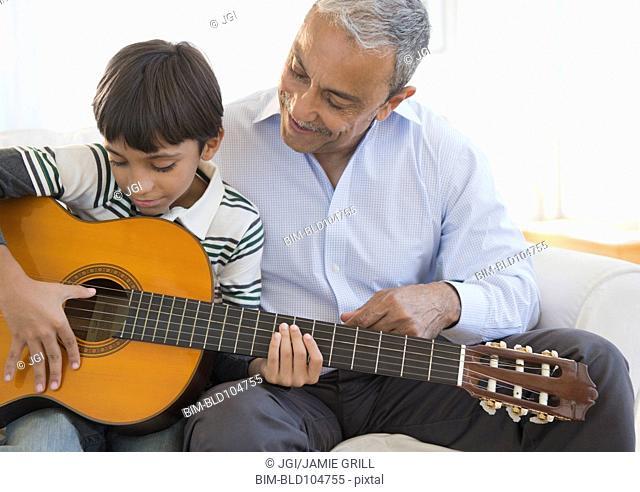 Hispanic grandfather watching grandson playing guitar