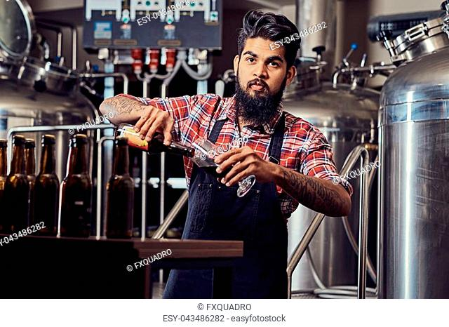 Stylish full bearded Indian man in a fleece shirt and apron pours beer in a glass for quality control, standing behind the counter in the brewery