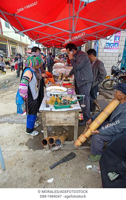 China , Yunnan province , Yuanyang , Duoyishu village, market , Yi people are in colored dress , Hani people are in dark blue and black , tobacco