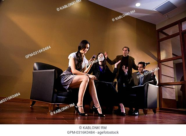 Sexy businesswoman holding cell phone while three other colleagues look on