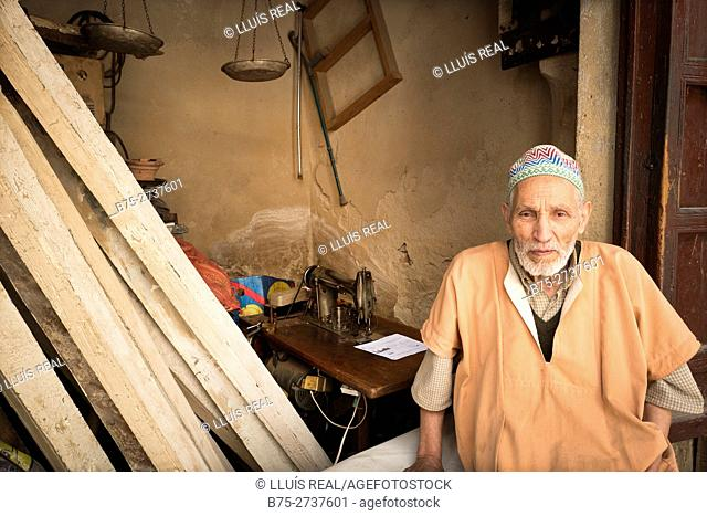Portrait of Moroccan man in traditional costume beside sewing machine. Fez, Morocco