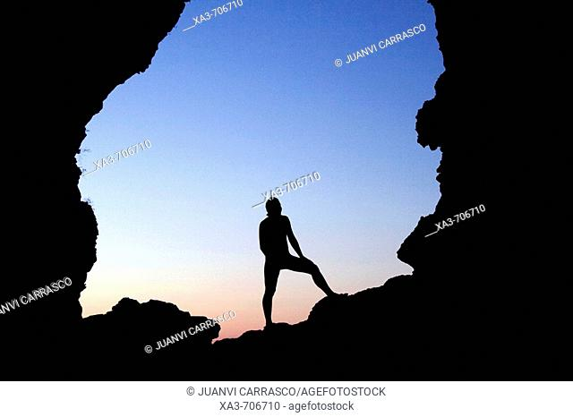 Silhouette of person at the entrance of a cave
