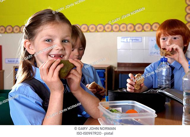 School children eating packed lunches