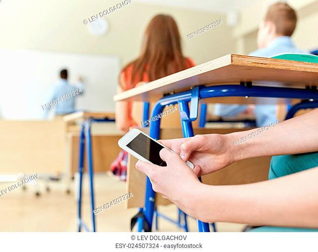 education, high school, learning, technology and people concept - student boy hands with smartphone texting on lesson