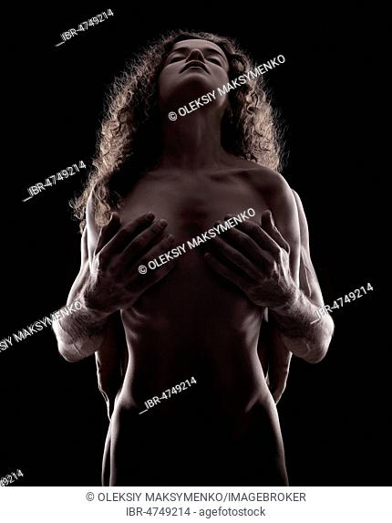 Sensual artistic nude portrait of a couple making love, naked woman silhouette with man hands covering her breasts, Canada