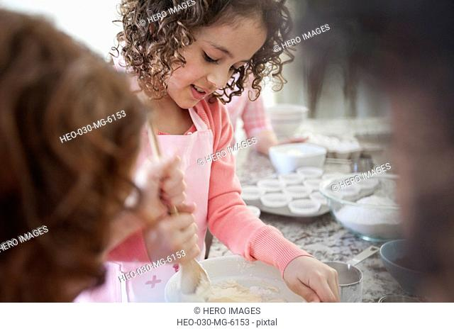 young girls stirring batter
