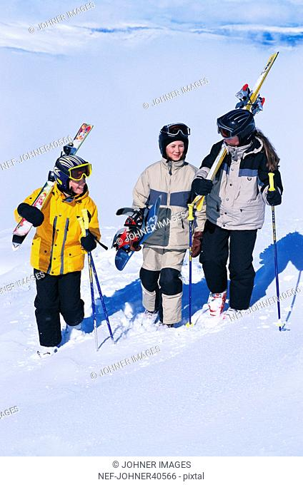 Three children trudging in snow carrying snowboard and slalom skis