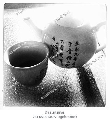 closeup of a teapot and cup of tea, with inscriptions in Chinese on a glass table