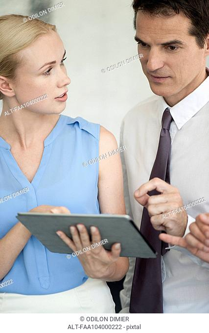 Business associates using digital tablet together