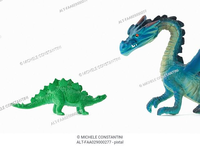 Toy dinosaur facing toy dragon